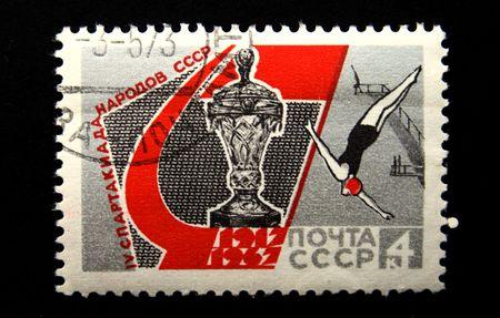 springplank: Een stempel gedrukt in de Sovjet-Unie gewijd Games van mensen van de USSR, toont sportman duiken vanaf een springplank en een prijs van Games, omstreeks 1967