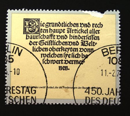 revolt: A stamp printed in DDR (East Germany) devoted 450 anniversary of German farmers revolt show The description of history of revolt, one stamp from series, circa 1970s
