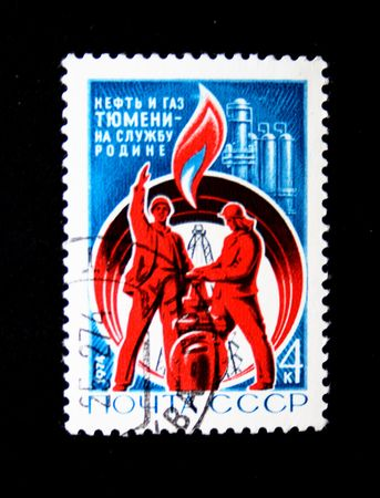 A stamp printed in USSR Shows two workers on a background of an oil derrick, the pipeline and an oil refining factory, have inscripr cruid oil and natural gas of Tumen, circa 1974. photo