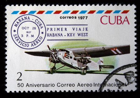 avia: A stamp printed in Cuba shows vintage airplane and devoted first passenger flight from Habana to Key West, stamp from series honoring 50 years of Cuban international AVIA post, circa 1977