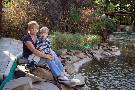 Grandmother and grandson sitting on the pond Stock Photo - 7632934