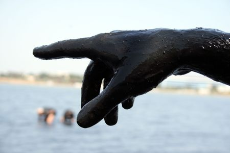 saki: dirty  hand covered with mud on background of the salty lake, the town of Saki, Crimea, Ukraine