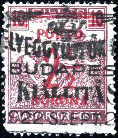 HUNGARY - CIRCA 1922 A stamp printed in Hungary shows woman harvesting, circa 1922 Stock Photo - 7687455