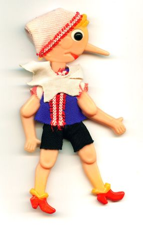 antique toy Pinocchio puppet with a long nose on a white background photo