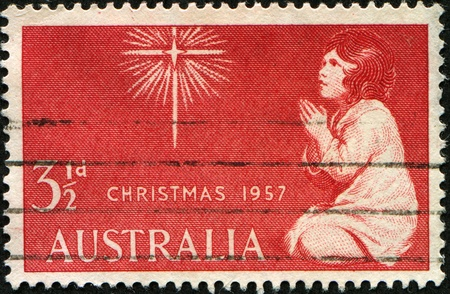 australia stamp: AUSTRALIA - CIRCA 1957: A Christmas stamp printed in Australia showing an image of a girl praying to a star, circa 1957 Stock Photo