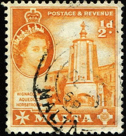 MALTA - CIRCA 1956: A stamp printed in Malta shows Queen Elizabeth II and Wignacourt aqueduct horsetrough, circa 1956
