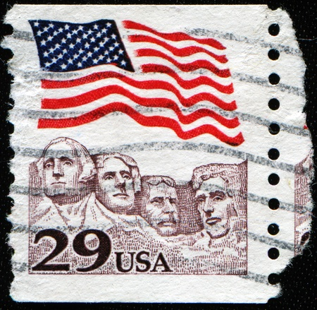 'mt rushmore': UNITED STATES OF AMERICA - CIRCA 1991: A stamp printed in the USA shows American flag waving proudly above Mt. Rushmore, circa 1991