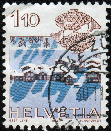 helvetica: SWITZERLAND - CIRCA 1983: A stamp printed Switzerland, officially Confideratio Helvetica, shows Zodiac sign Pisces on the background image of winter village, circa 1983.
