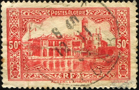 constituting: ALGERIA - CIRCA 1930: A stamp shows The flagship of the Admiralty lies on one of the islands constituting the historic coastline of the city of Algiers