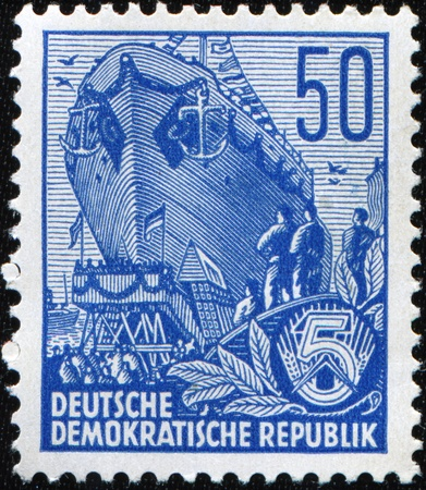 GERMANY- CIRCA 1953: A stamp printed in GDR (East Germany) shows Building the multi-purpose dry cargo sea-river going vessels, circa 1953.  photo