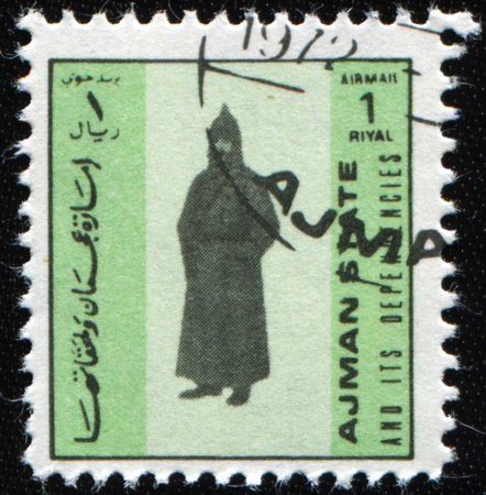 ajman: AJMAN - CIRCA 1972: A stamp printed in Ajman shows Red Army soldier in a greatcoat and Budenovka, circa 1972