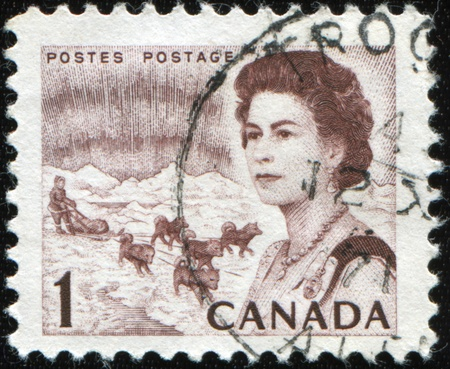 CANADA - CIRCA 1971: A post stamp printed in Canada shows Portrait of Elizabeth 2 on the background of male control dog team, circa 1971