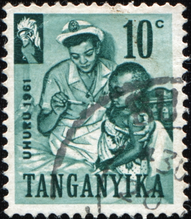 tanganyika: TANGANYIKA - CIRCA 1961: A stamp printed in Tanganyika shows nurse hugging a black girl, sitting on the bed and looked at the thermometer, circa 1961 Stock Photo