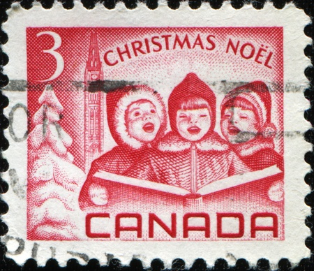 canada stamp: CANADA - CIRCA 1967: A stamp printed in Canada  shows three singing child with a book in their hands against the backdrop of the Christmas tree and the parliament, circa 1967