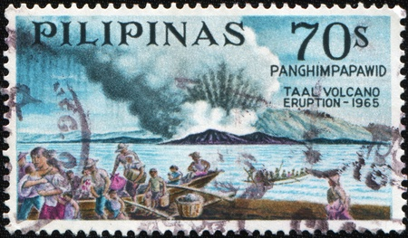 PHILIPPINES - CIRCA 1967: A stamp printed in Philippines shows Taal volcano eruption - 1965, circa 1967 photo