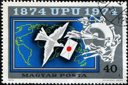homing: HUNGARY - CIRCA 1974: A post stamp printed in Hungary shows homing pigeon with a letter in its beak against the backdrop of the Earth, circa  1974