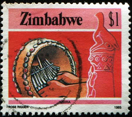soapstone: ZIMBABWE - CIRCA 1985: A stamp printed in Zimbabwe shows Playing Mbira (musical instrument) at the right Zimbabwe Bird soapstone sculpture, circa 1985