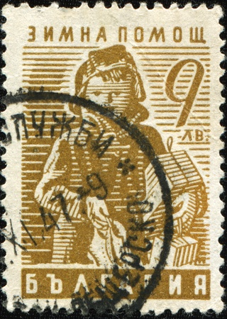 BULGARIA - CIRCA 1947: A stamp printed in Bulgaria SHOWS Child carrying gifts, circa 1947 Stock Photo - 9293132