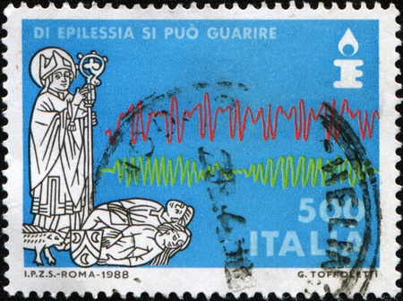 ilness: ITALY - CIRCA 1988: A stamp printed in Italy dedicated to recovery from epilepsy shows a priest reading a prayer over the two ilness, circa 1988 Stock Photo