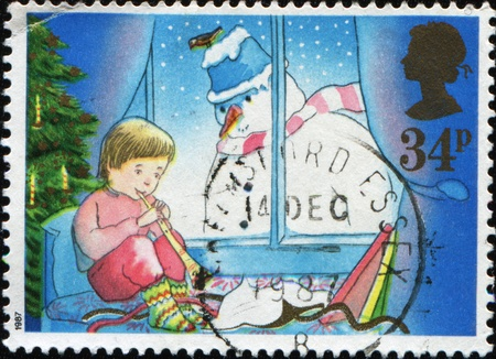 GREAT BRITAIN - CIRCA 1987: A greeting Christmas stamp printed in Great Britain shows boy sitting on the bed under the Christmas tree and playing a pipe, into the window looks a snowman, circa 1987 photo