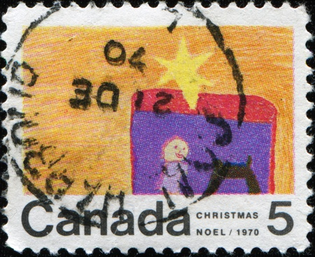 CANADA - CIRCA 1970: A greeting stamp printed in Canada shows childs picture with the star that appeared in the sky after the birth of Jesus Christ, circa 1970 photo