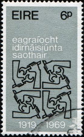 quadruple: IRELAND - CIRCA 1969: A stamp printed in Ireland honoring 50th Anniversary of International Labor Organization shows Quadruple I.L.O. Emblems, circa 1969