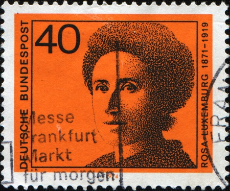 economist: GERMANY - CIRCA 1974: A stamp printed in the German Federal Republic shows Rosa Luxemburg - Marxist theorist, philosopher, economist and activist of Polish Jewish descent who became a naturalized German citizen, circa 1974 Stock Photo