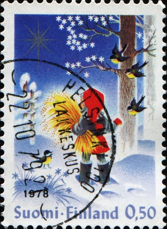 FINLAND - CIRCA 1992: A Christmas stamp printed in Finland shows boy in red hat in winter forest, circa 1992 Stock Photo - 9840886