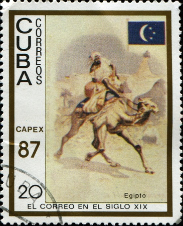 camel post: CUBA - CIRCA 1987: A post stamp printed in Cuba shows postman on camel, Egypt, end of XIX century. circa 1987