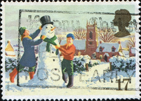 GREAT BRITAIN - CIRCA 1990: A stamp printed in Great Britain shows children are building a snowman, series is devoted to Christmas, circa 1990  photo