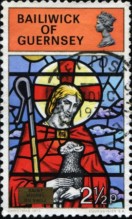 guernsey: GUERRENCEY - CIRCA 1973: A Christmas greeting stamp printed in Guernsey shows Stained-glass Windows from Guernsey Churches  Stock Photo