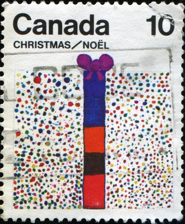 CANADA - CIRCA 1975: A greeting stamp printed in Canada shows childs picture with the gift, circa 1975 photo