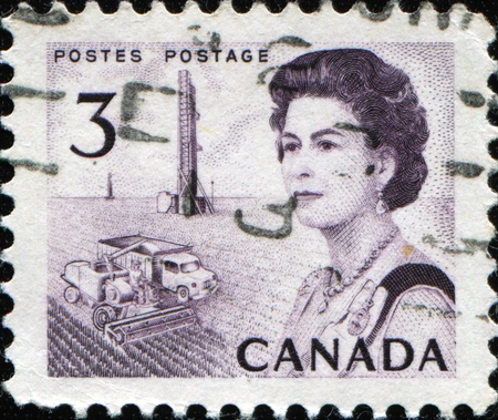 CANADA - CIRCA 1972: A post stamp printed in Canada shows Queen Elizabeth II on the background of harvsting, circa 1972