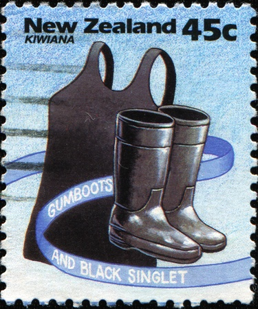 gumboots: NEW ZEALAND - CIRCA 1994: A stamp printed in New Zealand shows gumboots and black singlet, Kiwiana series, circa 1994
