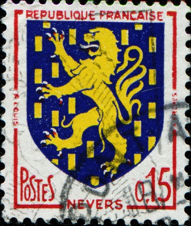 FRANCE - CIRCA 1960: A stamp printed in France shows coat of arms of Nevers - the administrative capital of the Nièvre department in the Bourgogne region in central France, circa 1960 photo