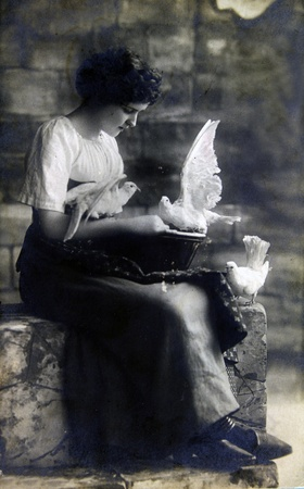 GERMANY - CIRCA 19100: Postcard printed in the Germany shows Woman sitting on stone steps, feeding white doves, circa 1910