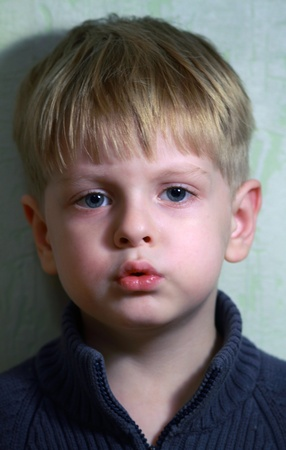 A portrait of a young boy looking into camera photo