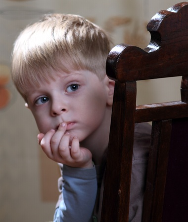 little boy looks out from behind the antique chair  Stock Photo