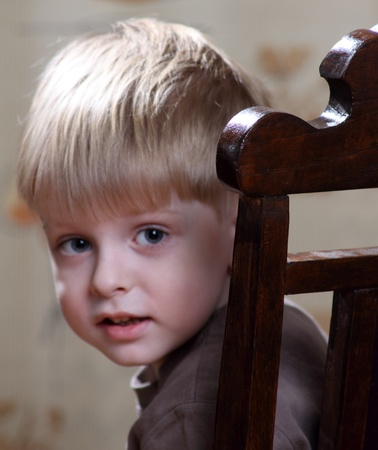 little boy looks out from behind the antique chair  photo
