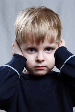 boy puts his hand over his ears Stock Photo