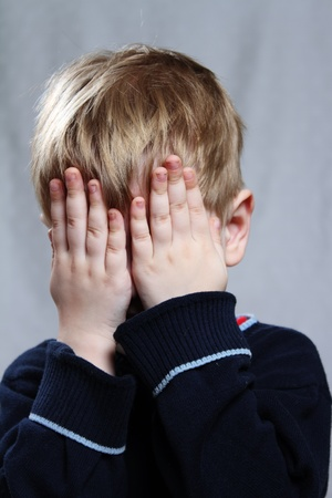 boy puts his hand over his eyes photo