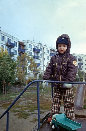 little boy standing on a hill in the background of a multistory building, Kursk, Russia, 1981 Stock Photo - 13002990