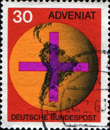 GERMANY - CIRCA 1967: A stamp printed in Federal Republic of Germany honoring Adveniat - Aid for Catholic Church in Latin America, shows Cross on South American Map, circa 1967 photo