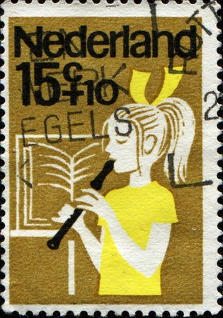 NETHERLANDS - CIRCA 1964: A stamp printed in  Netherlands shows a girl playing the flute, circa 1964 Stock Photo - 13345296