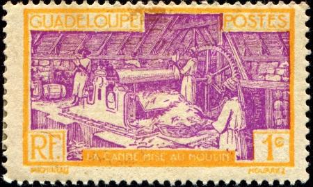 GUADELOUPE - CIRCA 1928: stamp printed in Guadeloupe shows Sugar Refinery, circa 1928 photo