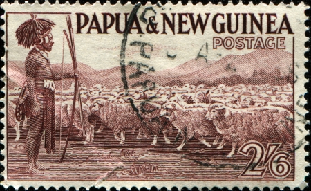 Papua New Guinea - CIRCA 1952: A stamp printed in Papua New Guinea shows shepherd with a flock of sheep, circa 1952 photo