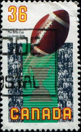 canadian football: CANADA - CIRCA 1987  A stamp printed in Canada honoring 75th Grey Cup Final  Canadian football championship , Vancouver, shows Football, Grey Cup and Spectators, circa 1987 Editorial