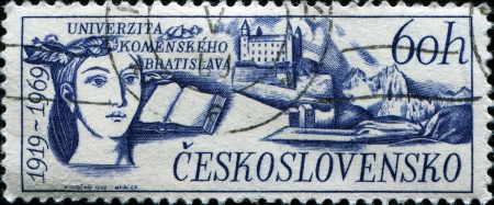 CZECHOSLOVAKIA - CIRCA 1969  A stamp printed in Czechoslovakia honoring 50th Anniversary Comenius University, shows Bratislava Castle, open book and head of woman , circa 1969 photo