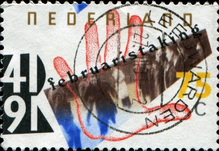 raid: NETHERLANDS - CIRCA 1991  A stamp printed in Netherlands honoring 50th Anniversary of Amsterdam General Strike, shows German Raid on Amsterdam Jewish Quarter and Open Hand, circa 1991 Stock Photo