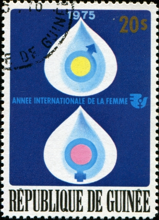 guinee: GUINEE - CIRCA 1975  a stamp printed in the Guinee honoring International Womens Year 1975,shows Genetics emblems, circa 1975  Stock Photo